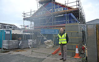 james vivian standing infront of building site for the construction of 2 flats in threemilestone