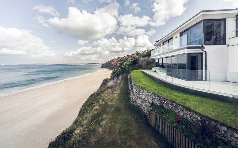 contemporary coastal house on the cliff at carbis bay cornwall with flat natural sedum roof, white rendering & 180 degree views out to the bay